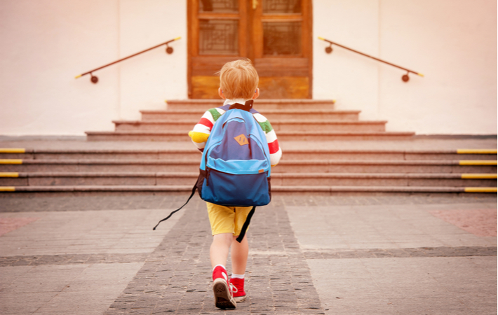 little boy with blue backpack going to school
